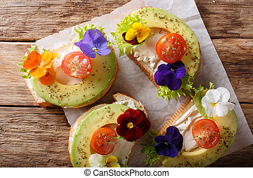 Sandwiches with edible flowers, fresh avocado and cream cheese close-up. horizontal top view