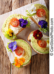 Sandwiches with edible flowers, fresh avocado and cream cheese close-up. Vertical top view