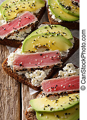 sandwiches with fillet of tuna, avocado and cream cheese close-up. vertical
