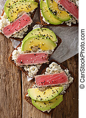 sandwiches with fillet of tuna, avocado and cream cheese close-up. Vertical top view