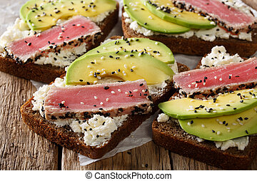 sandwiches with fried tuna in sesame, fresh avocado and cream cheese close-up. horizontal