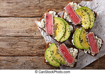 sandwiches with fried tuna in sesame, fresh avocado and cream cheese close-up. Horizontal top view