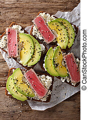 sandwiches with fried tuna in sesame, fresh avocado and cream cheese close-up. Vertical top view