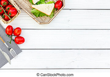 Sandwiches with lettuce and tomato for picnic on tablecloth on white wooden table background top view copyspace