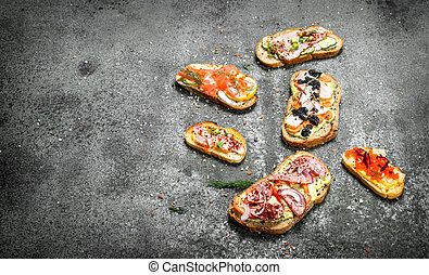 Sandwiches with meat, salami, seafood and fresh vegetables.