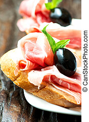 Sandwiches with prosciutto olive on plate