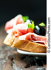 Sandwiches with prosciutto olive on plate vertical