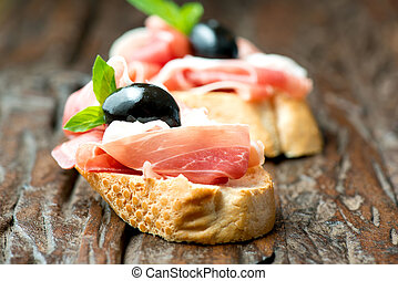 Sandwiches with prosciutto olive on wooden old table horizontal