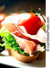 Sandwiches with prosciutto on plate close up