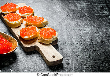 Sandwiches with red caviar on a wooden cutting Board.