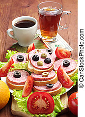 Sandwiches with sausage, cup of coffee and tea