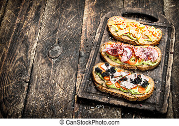 Sandwiches with seafood, salami, cheese and vegetables.