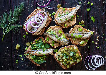 sandwiches with sprats on a background fennel and greens on a black background