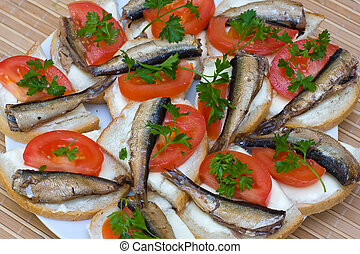 Sandwiches with sprats on a plate