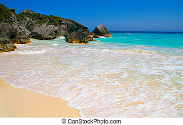 Sandy beach and rocky coastline with blue ocean water (...