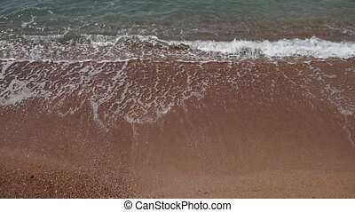 Sandy beach and waves, close-up. Texture of sand and water....