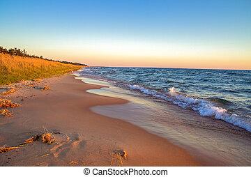Beautiful sandy beach stretches to the blue sky horizon.