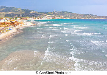 sandy beach background with turquoise sea water waves, Greece