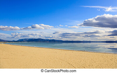 Sandy beach, calm sea, blue sky with few white clouds background. Summer destination. Reflection on sea of clouds and mountains.
