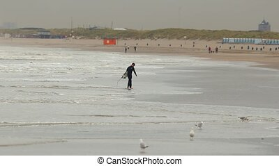 ROTTERDAM, THE NETHERLANDS - CIRCA 2019: Surfer coming out from the sea at the sandy beach of the Hook of Holland, popular recreational area at the North Sea