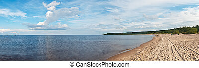 Sandy beach of Ladoga Lake with traces of automobile tires.