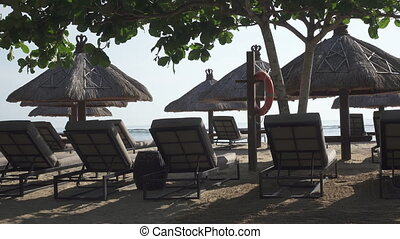 Sandy beach of the tropical resort with umbrellas and chaise lounges