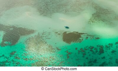 Sandy beach with tourists among turquoise waters and coral reefs. Beach at the atoll. Summer and travel vacation concept. Balabac, Palawan, Philippines.
