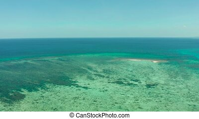Small sandy beach on a coral atoll in turquoise water, aerial view. Summer and travel vacation concept. Balabac, Palawan, Philippines.