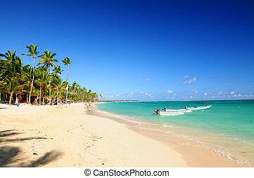 Sandy beach on Caribbean resort and fishing boats at sea