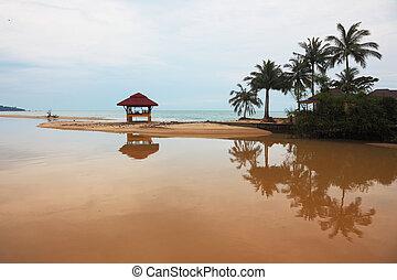 Sandy beach on Koh Samui. Swimwear wooden gazebo beautifully reflected in the water