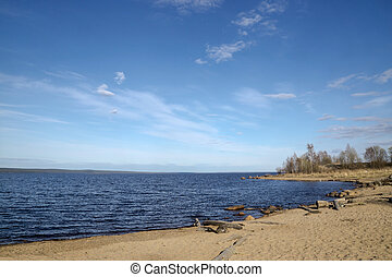 Sandy beach on lake in sunny day