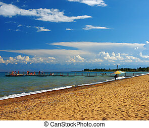 Sandy beach with a pier against the blue sky of the sea and far mountains