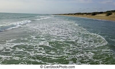 Sandy beach with choppy rough sea under dense clouds...