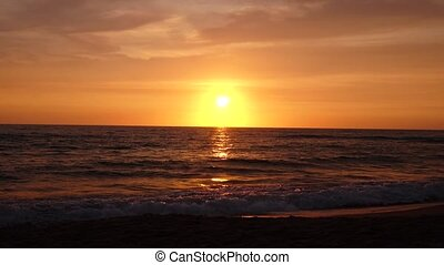 Sandy beach with choppy waves of the sea at sunset - Sandy...