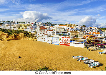 Sandy beach with colorful boats and cliffs and white architecture in Carvoeiro, Algarve, Portugal