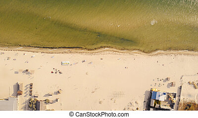 Sandy beach with sunbathing tourists, view from drone.
