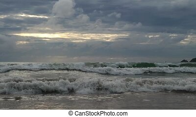 sandy beach with waves at sunset, thunderclouds on a sky....