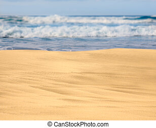 Smooth and sandy beach leading into the distance with waves