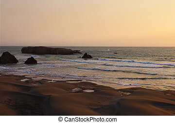 Sandy coast of the Pacific Ocean during sunset, sunrise