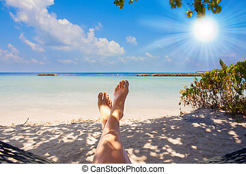 sandy feet on the beach with clear ocean water under sun