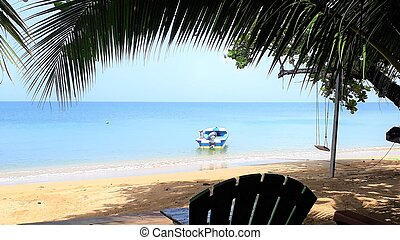 Sandy palm tree beach with blue sea, a seat and a boat