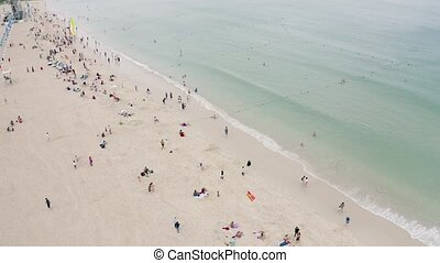 Sandy sea beach - Sandy beach with tourists swimming and tan...