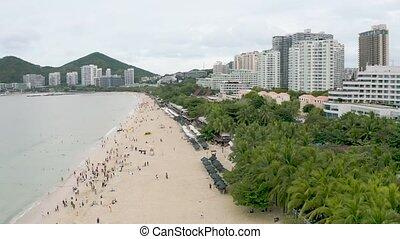 Sandy sea beach - Sandy beach with tourists swimming in sea ...
