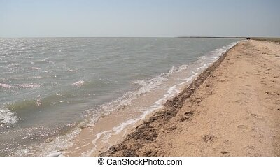 Sandy sea shore on a sunny day with waves lapping on empty...