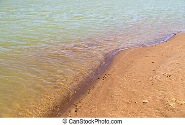 Sandy shore on the river as a background