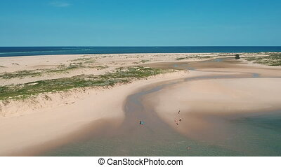 Sandy Shore with Blue Sea in Horizon and People on Sand