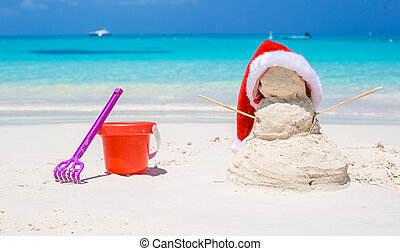Sandy snowman with red Santa Hat and beach toys