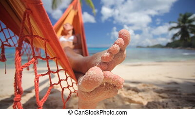 sandy toes in changing light - sandy toes of woman relaxing...