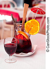Traditional Spanish wine beverage sangria with strawberries, orange and ice on a table in cafe.