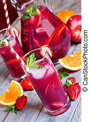 Sangria with strawberry, mint and orange in glasses and pitcher. Selective focus.